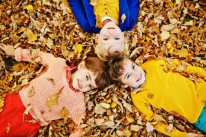 Above view of three smiling children, two boys and girl, in bright clothes enjoying warm autumn day, playing in park and lying in pile of fallen leaves and looking at camera